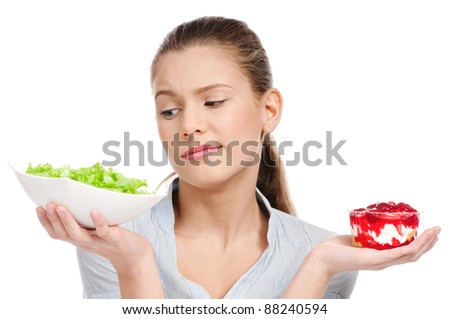Pretty young woman choice lettuce salad or cake. Isolated on the white background