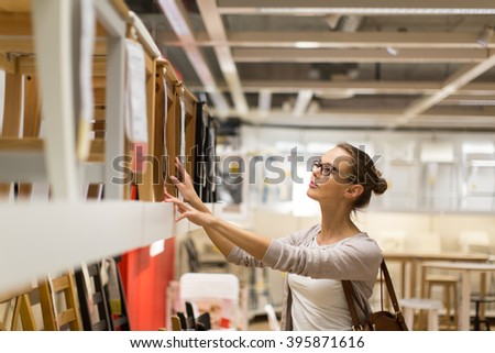 Pretty, young woman choosing the right furniture for her apartment in a modern home furnishings store (color toned image; shallow DOF) - stock photo