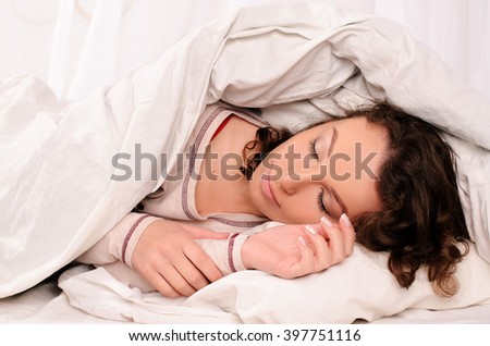 pretty young woman covered with blanket sleeping on bed with white bedding