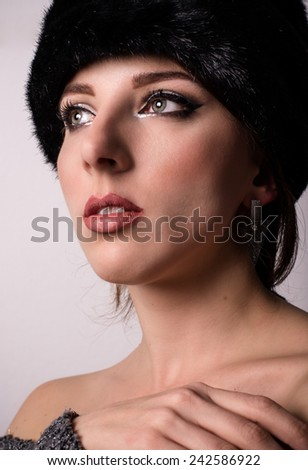 Pretty young woman daydreaming in a winter fur hat looking up off to the side with her hand raised to her chest and a meditative expression - stock photo