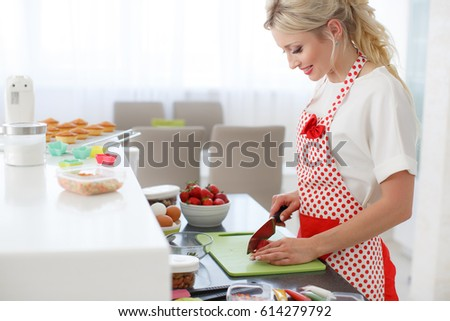 Woman Decorating Cupcakes pretty young woman decorating cupcakes on stock photo 604861793