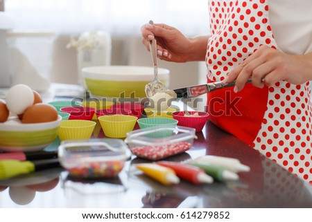 Woman Decorating Cupcakes pretty young woman decorating cupcakes on stock photo 614279810