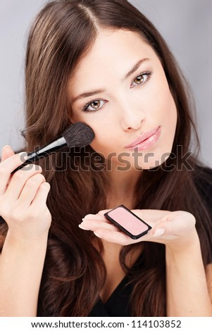 pretty young woman doing make up with powder brush - stock photo