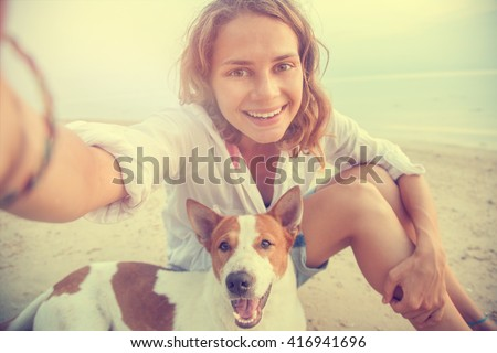 pretty young woman doing selfie with her dog on the beach at sunset - stock photo