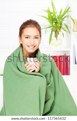 pretty young woman drinking tea  at home covered with blanket - stock photo