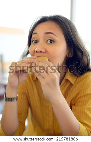 Pretty Young Woman Eating Burger Enjoying Break Lunch In Cafe - stock photo