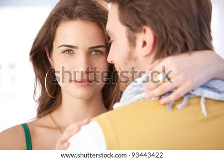 Pretty young woman embracing man, smiling at camera.? - stock photo