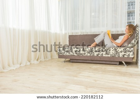 Pretty young woman enjoying reading a book at home lying on the sofa smiling in pleasure in casual clothing - stock photo