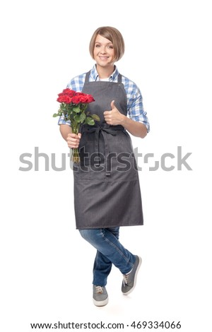pretty young woman florist in apron with red roses showing thumb up isolated on white background. proposing service. advertisement gesture. people, shopping, business and floristry concept
