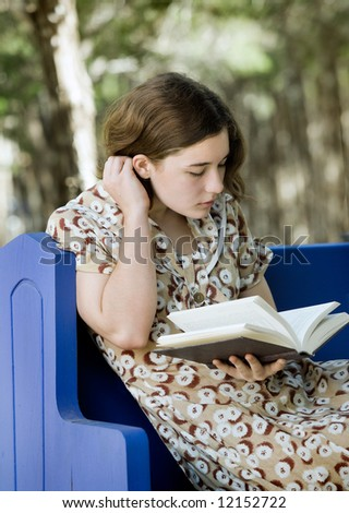 Pretty young woman/girl reading a book outdoors; soft focus portrait