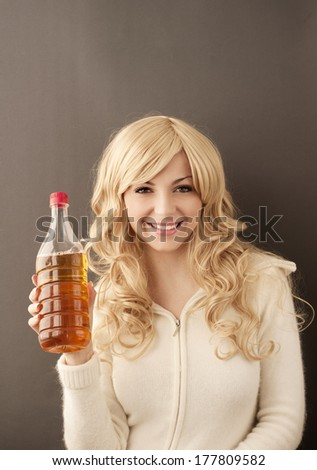 Pretty young woman holding a bottle of apple cider vinegar - stock photo