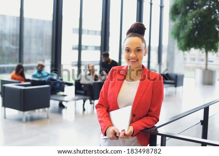 Pretty young woman holding a laptop standing by a railing looking at camera smiling. Young african american businesswoman in office with people sitting in background. - stock photo