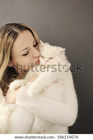 Pretty young woman holding a white cat - stock photo