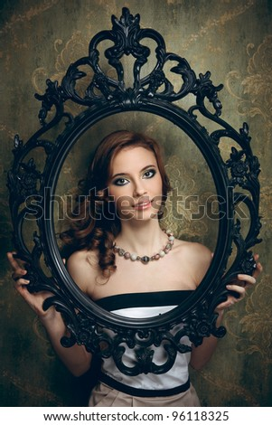 Pretty young woman holding an empty frame - stock photo