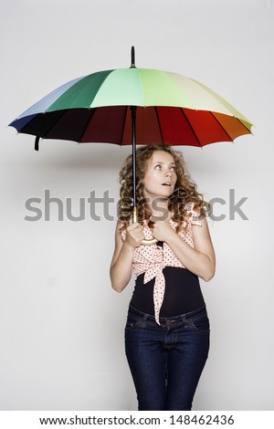 Pretty young woman holding an umbrella - stock photo