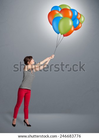 Pretty young woman holding colorful balloons - stock photo