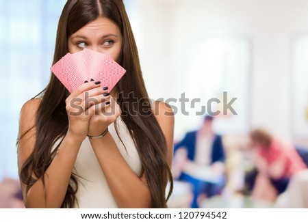 Pretty Young Woman Holding Playing Cards against an abstract background - stock photo