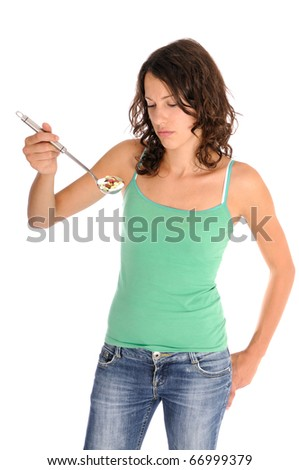 Pretty young woman holding spoon with pile of pills looking skeptical. Concept shot for drug abuse or alternative medicine. - stock photo