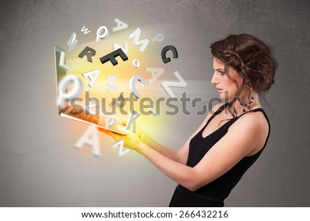 Pretty young woman hoolding notebook with colorful abstract letters - stock photo