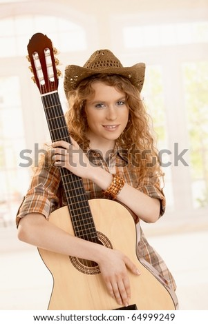 Pretty young woman hugging her guitar, dressed in country style.? - stock photo