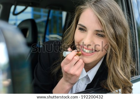 Pretty young woman in a car doing makeup. - stock photo