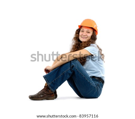 Pretty young woman in a hard hat sitting isolated on white background. Construction worker or intern concept. - stock photo