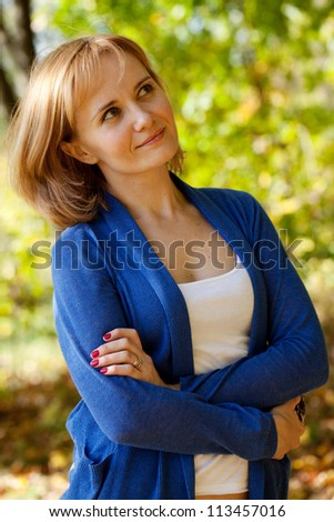 Pretty young woman in a sweater dreaming about something - stock photo