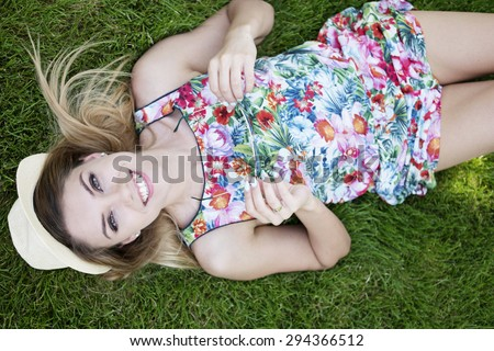 Pretty Young Woman in a Trendy Outfit Smiling at the Camera From High Angle View While Lying on the Green Grasses and Holding her Sunglasses. - stock photo