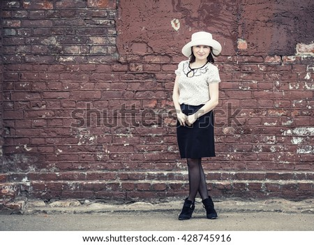 Pretty young woman in a white hat, blouse and black skirt, standing against old vintage brick wall background. Vintage portrait of a woman. Toned photo with copy space. Vintage style photo. - stock photo