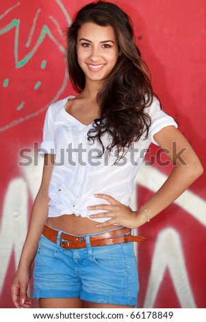 Pretty young woman in an outdoor lifestyle fashion pose. - stock photo