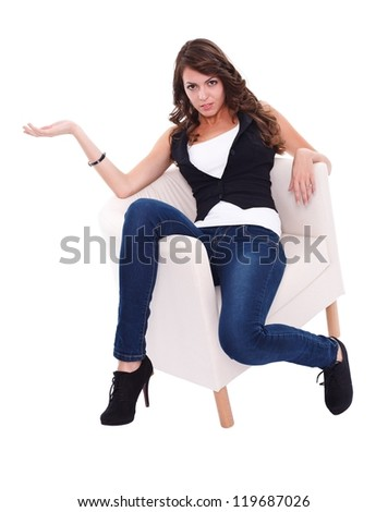 Pretty young woman in armchair posing to camera - stock photo