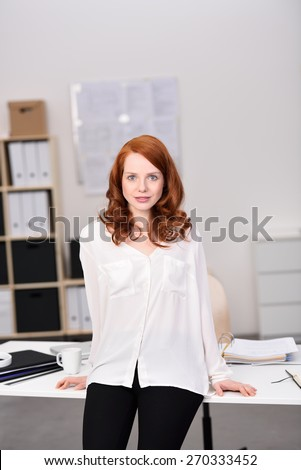 Pretty Young Woman in Black and White Outfit Leaning Back Against the Desk Inside the Office While Looking at the Camera. - stock photo