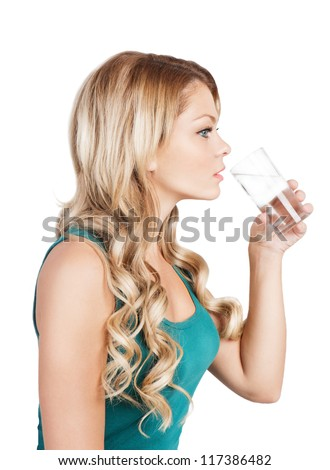 Pretty young woman in blue singlet is holding a glass of water. Beautiful blonde long-haired girl is drinking water from glass on white. Studio shot.