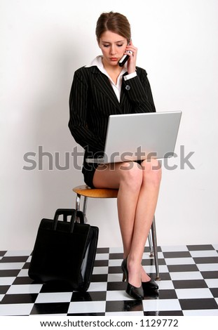 Pretty young woman in business attire talking on her cell phone and typing on her laptop computer - stock photo