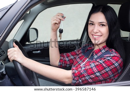 Pretty young woman in car holding and showing keys in hand - stock photo