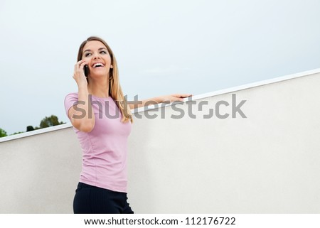Pretty young woman in casual wear smiling while attending phone call