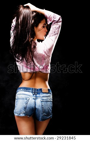pretty young woman in jeans shorts from back, studio shot - stock photo