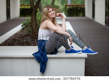 Pretty Young Woman in Leggings and Sneakers Outside - stock photo