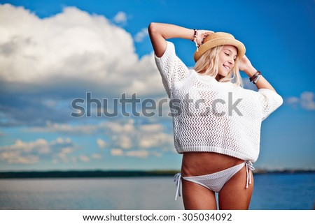 Pretty young woman in pullover and hat relaxing by the seaside - stock photo