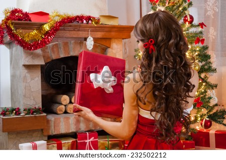 Pretty young woman in red and white christmas dress and long beautiful hair, holding a gift box near chimney and Christmas tree over living room. - stock photo
