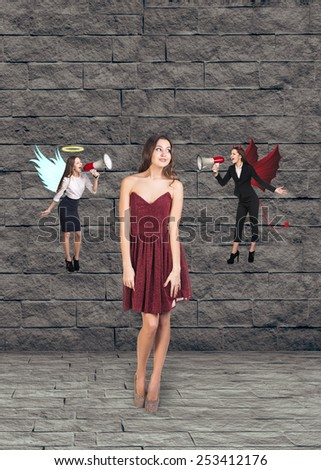 Pretty young woman in red dress thinks, an angel and a devil on grey brick background - stock photo