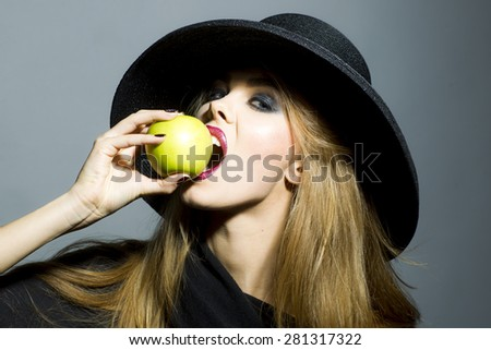Pretty young woman in retro black hat with bright make up biting fresh green apple standing on gray background copyspace, horizontal picture - stock photo