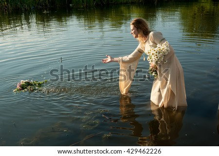 Pretty young woman in traditional dress puts wreath in water of lake. Russian traditional Ivan Kupala holiday celebration - stock photo