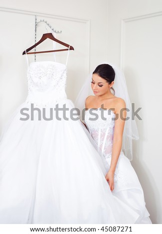 pretty young woman is choosing a wedding dress in the shop - stock photo