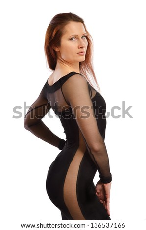 Pretty young woman is looking over shoulder. She is wearing a black cocktail dress with transparent insets. - stock photo