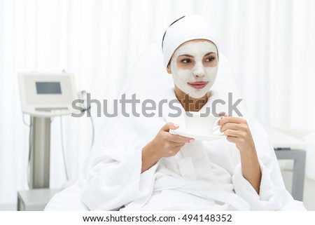 Pretty young woman is relaxing at spa salon. She is sitting with mask over face and drinking coffee. Girl is looking forward with joy