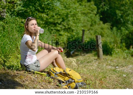 pretty young woman is resting during a hike in the French Alps