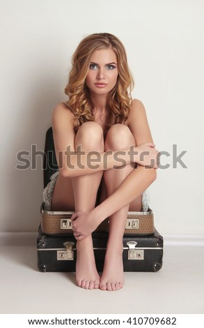 Pretty young woman is sitting on old leather suitcase. Beauty and Fashion girl.summer travel concept - stock photo