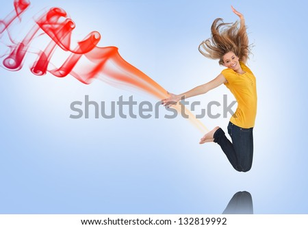 Pretty young woman jumping for joy with red and purple smoke trail on blue background - stock photo