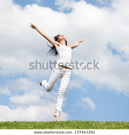 Pretty young woman jumping on green grass - stock photo